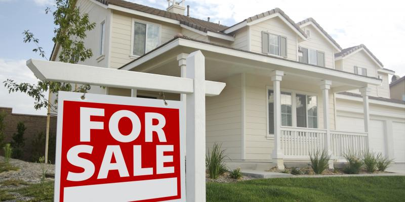 white home with a large front porch and a green front lawn with a for sale sign in front of it