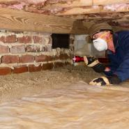 A-Action exterminator under a home inspecting for stinging insects