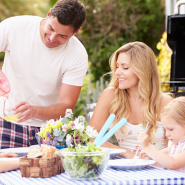 Family of four having a backyard BBQ. Dad is pouring water from a pink jug for his son