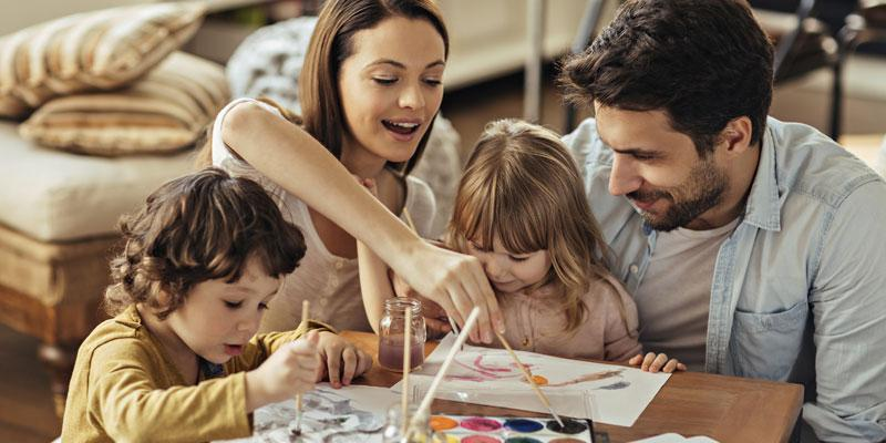 Family of four gathered on the floor around a wooden table painting watercolors and enjoying the lack of pests in their home thanks to A-Action Pest Control Exterminators