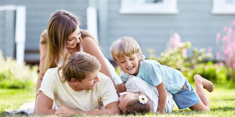 Family of four playing outside in their green lawn without worry of stinging insects thanks to the stinging insect control at A-Action Pest Control.